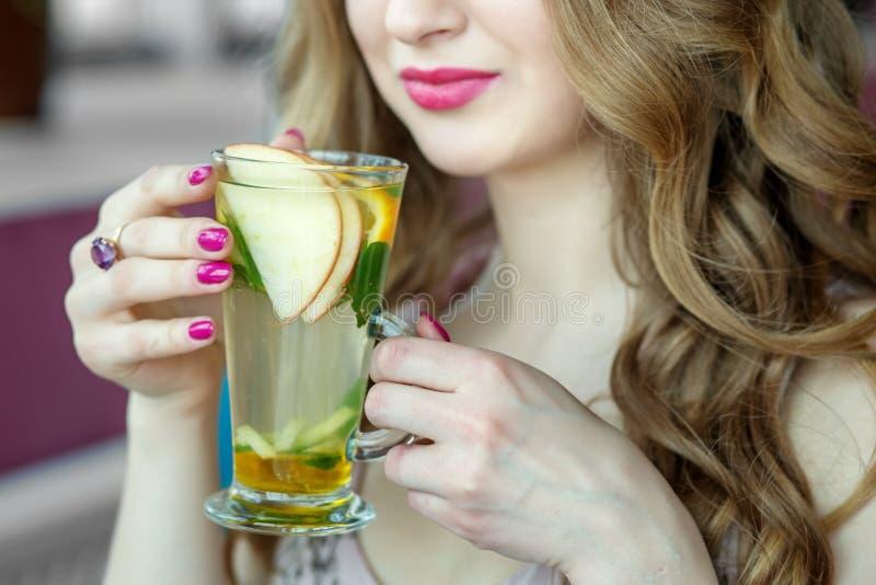 Taza de cristal de manos femeninas del té T? con la menta y la fruta c?trica Concepto de forma de vida, de bebidas y de consumici foto de archivo