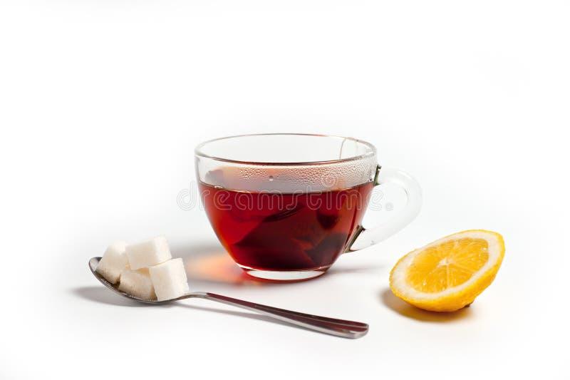 Taza de cristal para el té con una cuchara, una bolsita de té y un limón en un fondo blanco imagen de archivo