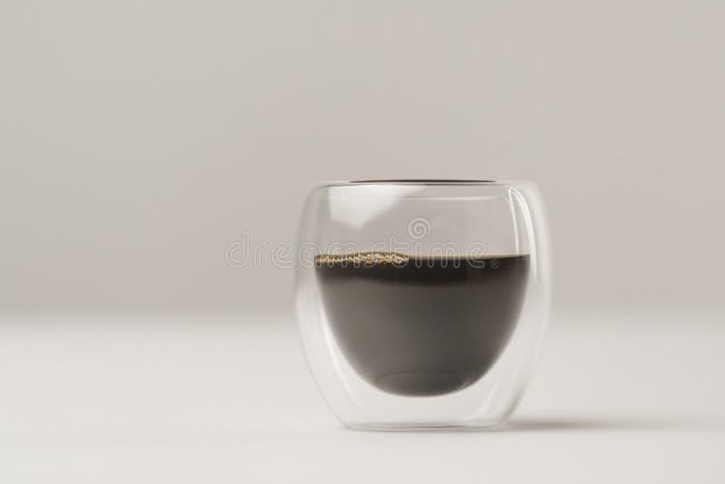 Taza de cristal de pared doble con café en el fondo blanco foto de archivo