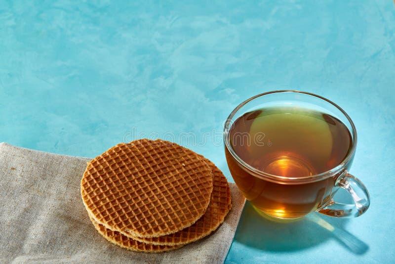Taza de cristal de primer del té y de las galletas en fondo azul fotografía de archivo