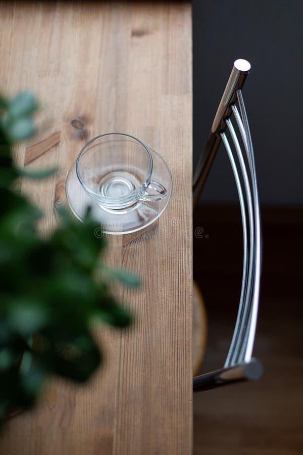 Taza de cristal vacía en la tabla de madera por la mañana imágenes de archivo libres de regalías