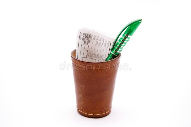 Taza de dados con el resbalón del bolígrafo del papel y imagenes de archivo