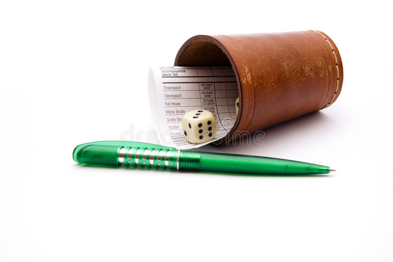 Taza de dados con el resbalón del bolígrafo del papel y fotos de archivo