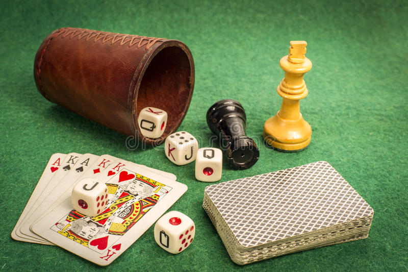 Taza de dados con las tarjetas de la cubierta y los pedazos de ajedrez fotografía de archivo