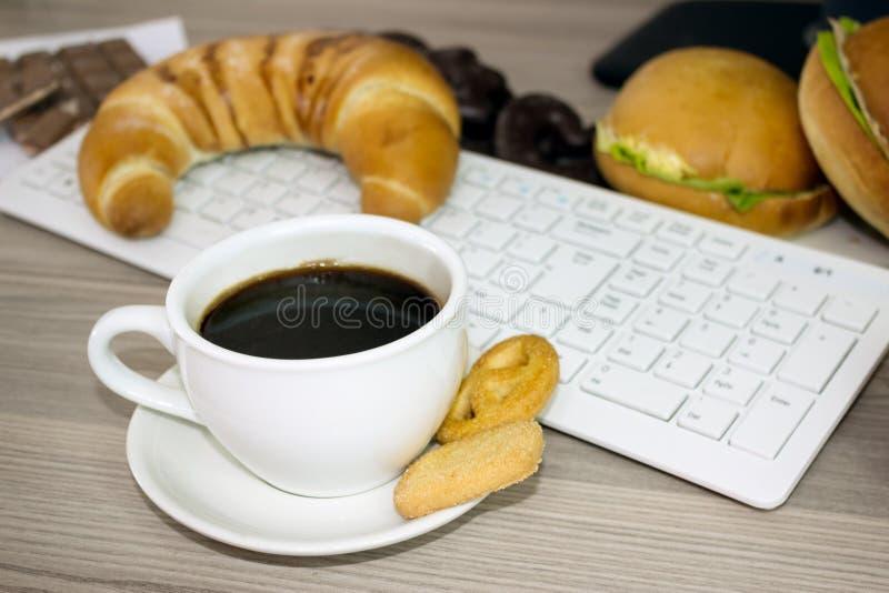 Taza de escritorio de las galletas del café y del chocolate con el ordenador fotos de archivo libres de regalías