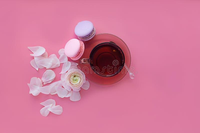Taza de flor del té y del macarrón y blanca en fondo rosado imagen de archivo