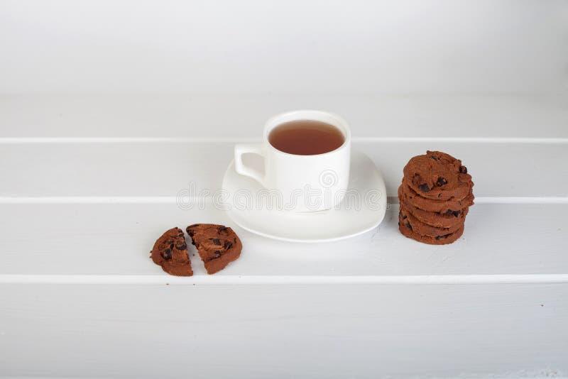 Taza de galletas de viruta del té y de chocolate fotos de archivo libres de regalías