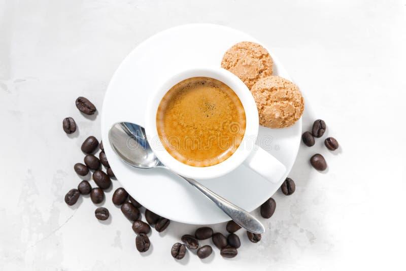 taza de galletas del café express y de almendra en una tabla blanca, visión superior fotografía de archivo