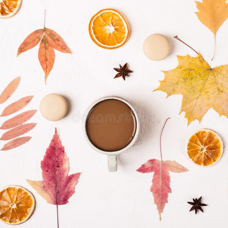 Taza de galletas del café y de los macarrones en la tabla blanca con el modelo de las hojas de otoño fotos de archivo