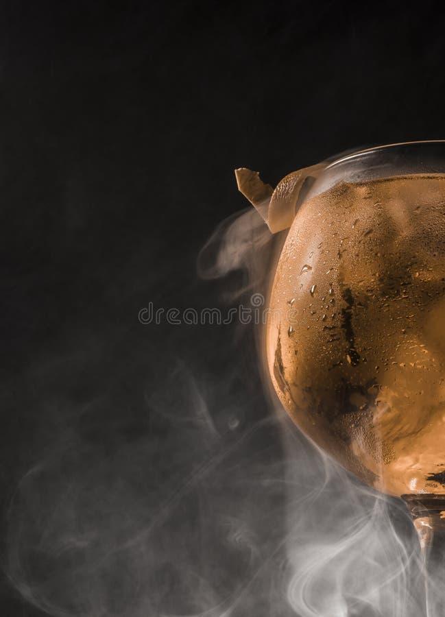 Taza de ginebra y de tónico mojados con humo y fondo oscuro fotos de archivo