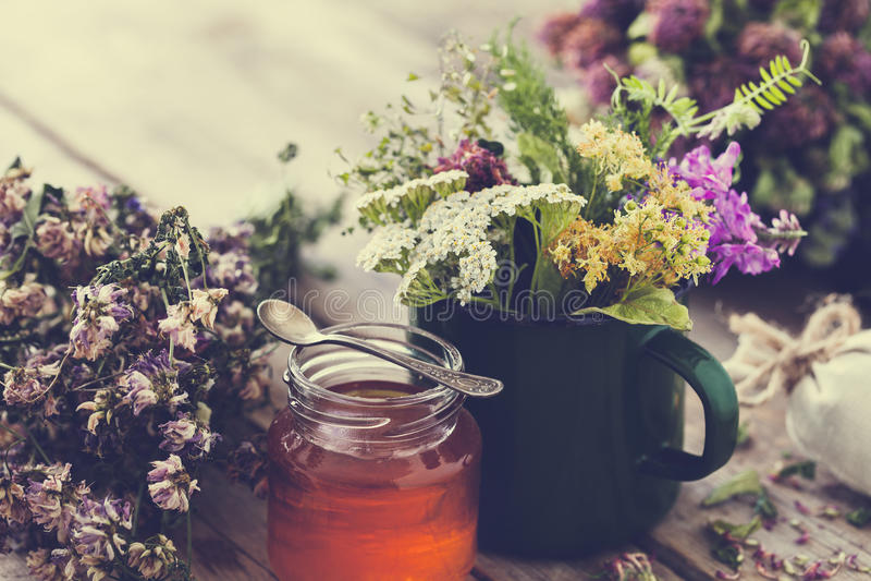 Taza de hierbas curativas, de caldera de té vieja, de tarro de la miel y de plantas medicinales fotografía de archivo