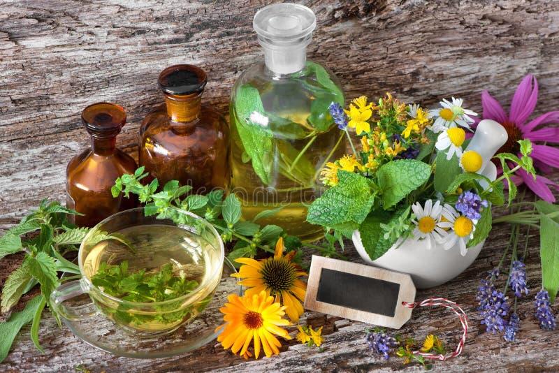 Taza de infusión de hierbas con las botellas medicinales y las hierbas curativas en el MES foto de archivo