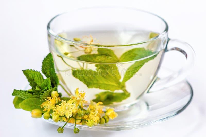 Taza de infusión de hierbas con las flores, la miel y la menta del tilo en la taza transparente aislada en blanco imagen de archivo