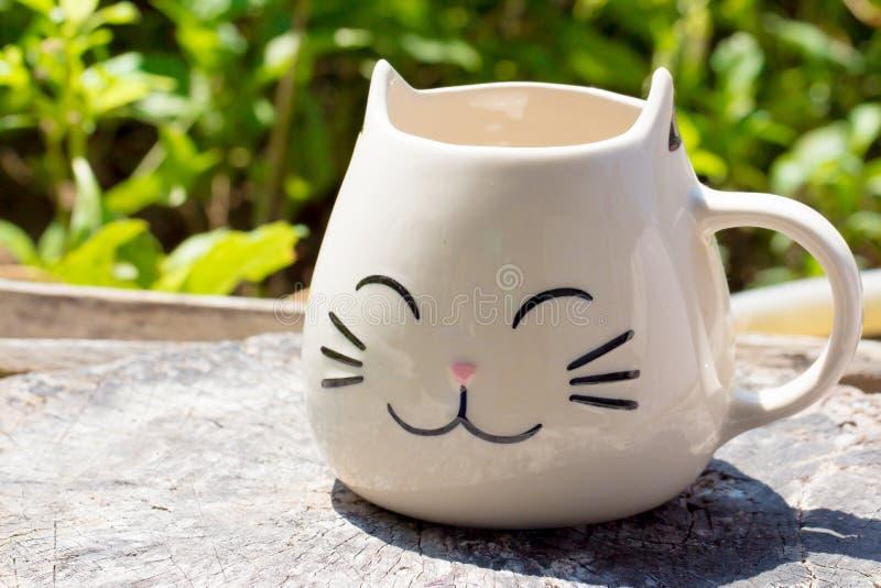 Taza de la cerámica de la forma del gato en la tabla de madera fotos de archivo