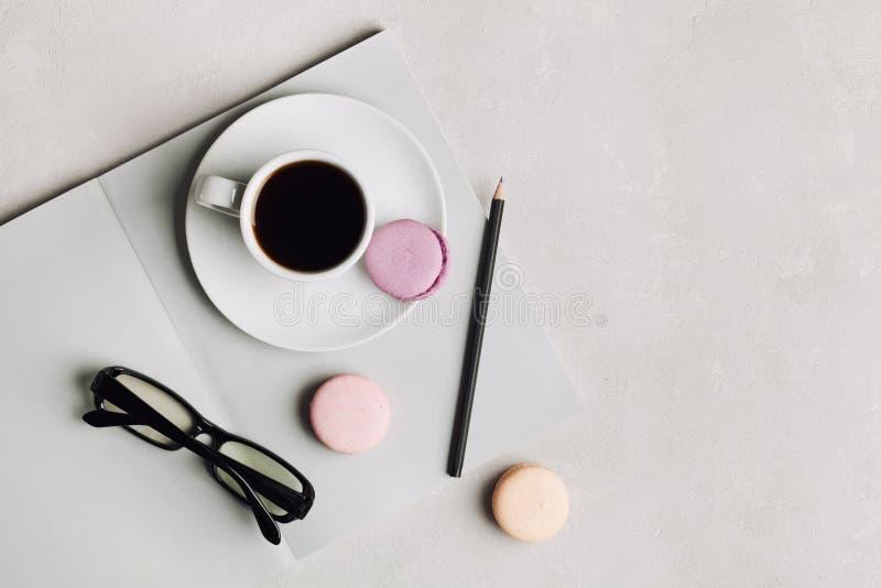 Taza de la mañana de café, de cuaderno vacío, de lápiz, de vidrios y de macaron de la torta en la opinión de arriba del escritori imagen de archivo