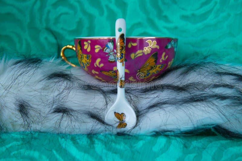Taza de la porcelana con el modelo y el fondo inclinado del naselennom de la cuchara foto de archivo