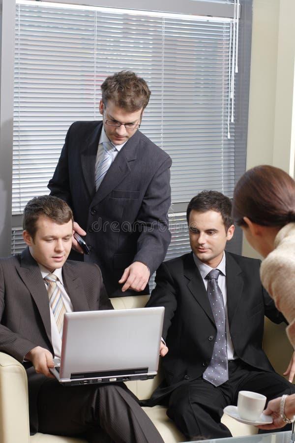 Taza de la porción de la secretaria de café a los hombres de negocios jovenes en la oficina fotografía de archivo libre de regalías