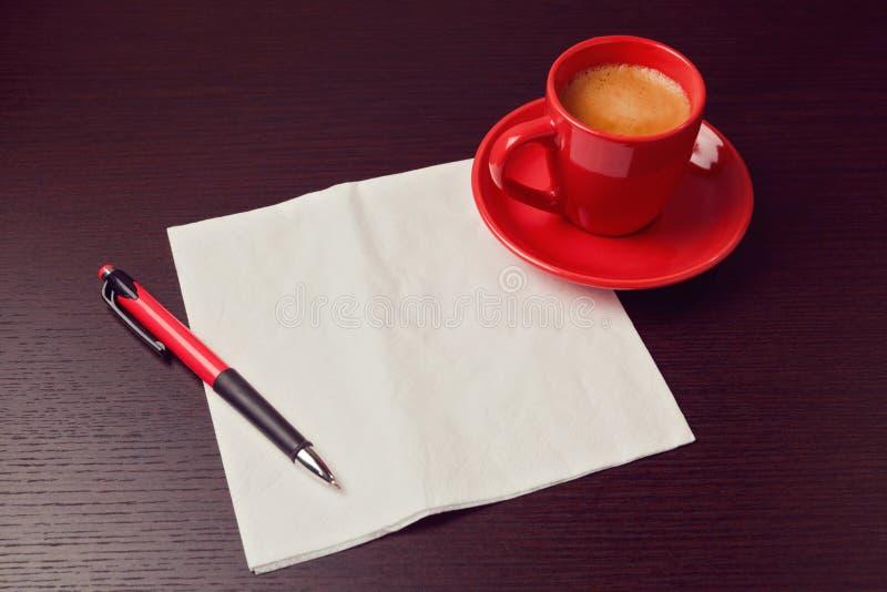 Taza de la servilleta y de café en el escritorio Mofa para arriba para la presentación del bosquejo fotografía de archivo libre de regalías