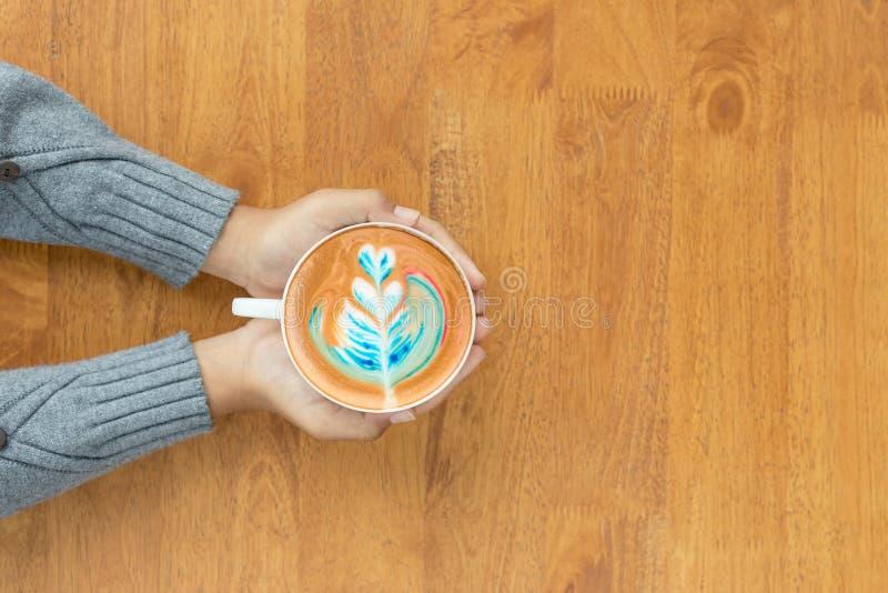 Taza de la tenencia de la mano de café caliente del arte del Latte en café reuni?n o socialice el concepto imagen de archivo libre de regalías