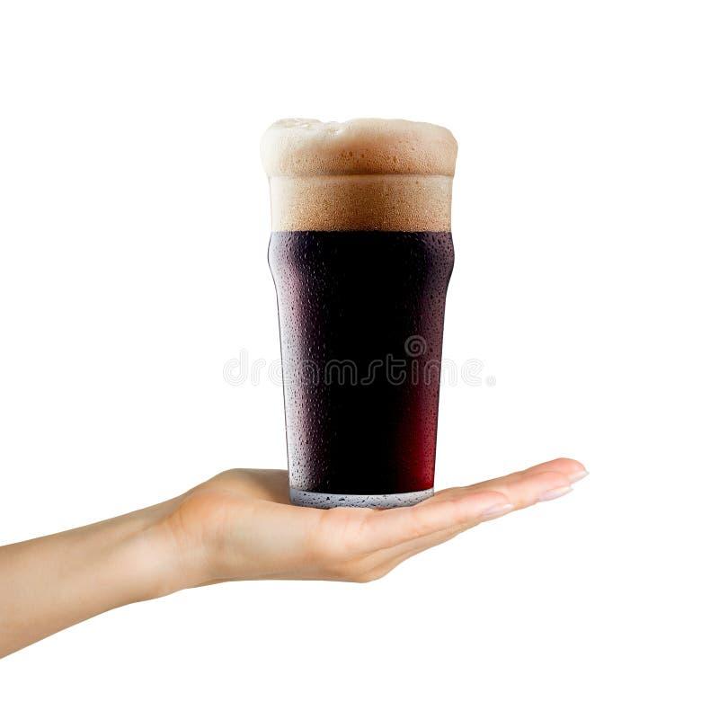 Taza de la tenencia de la mano de la mujer de cerveza con espuma en el fondo blanco imagenes de archivo