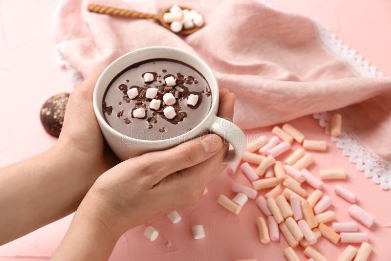 Taza de la tenencia de la mujer de chocolate caliente con las melcochas en fondo rosado imagen de archivo libre de regalías