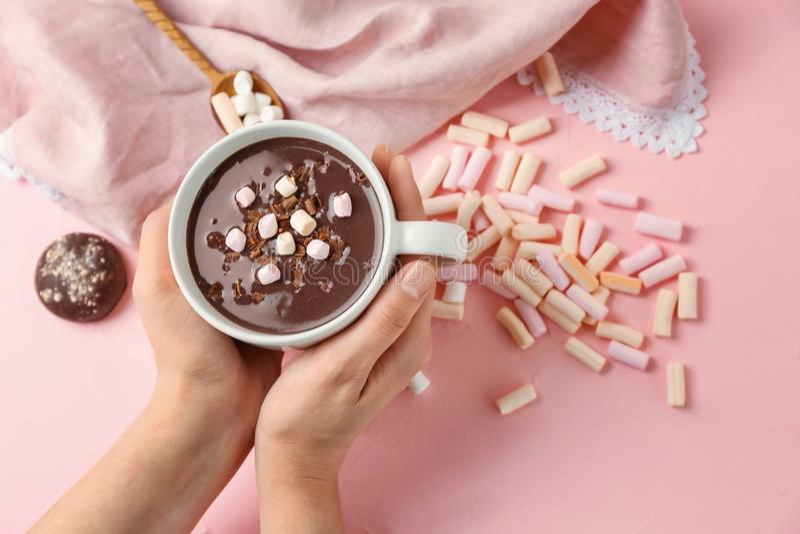 Taza de la tenencia de la mujer de chocolate caliente con las melcochas en fondo rosado fotos de archivo