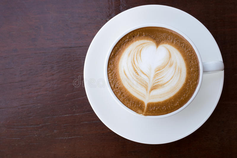 Taza de latte caliente del café con arte en forma de corazón de la espuma fotos de archivo