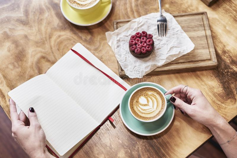 Taza de latte del café y de pasteles dulces en la tabla de madera en manos de la mujer las manos sostienen el cuaderno abierto, e fotografía de archivo
