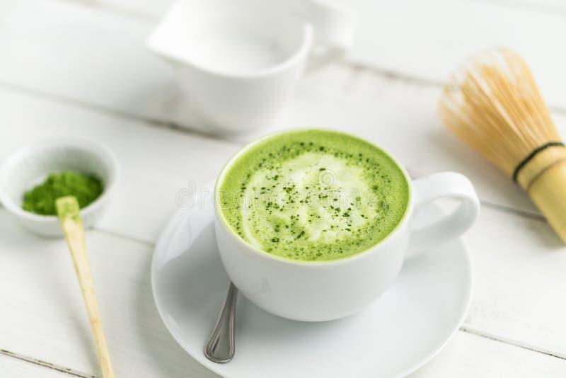 Taza de latte del té verde del matcha con los accesorios en fondo foto de archivo