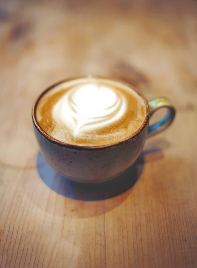 Taza de latte en la tabla imagen de archivo libre de regalías