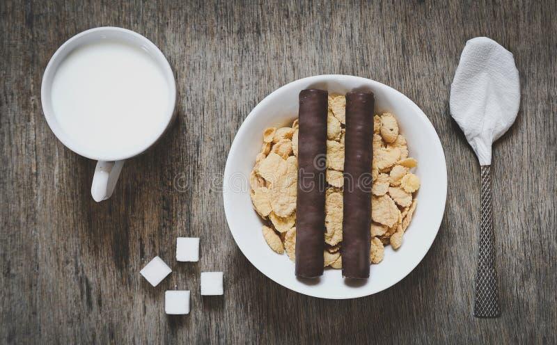 Taza de leche, de cubos del azúcar, de avenas con dos rollos de la oblea del chocolate y de cuchara en una tabla de madera fotografía de archivo