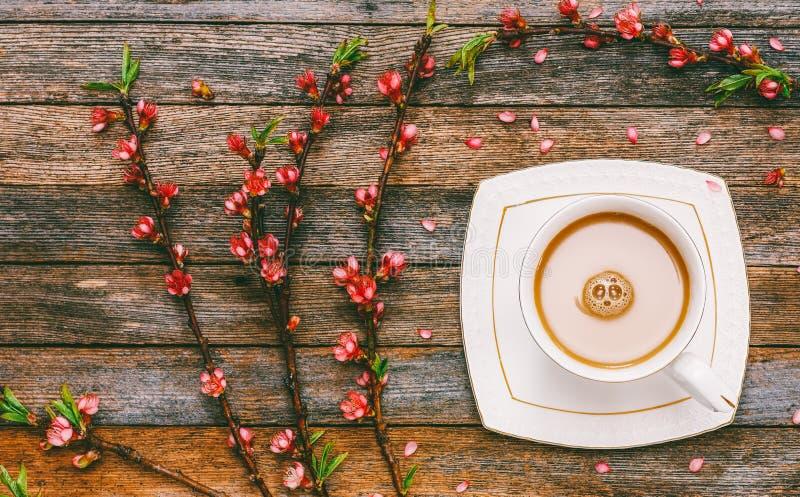 Taza de leche del café en una tabla de madera entre las ramas de un melocotón floreciente imagen de archivo