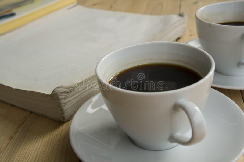 Taza de mañana del café con el libro fotografía de archivo