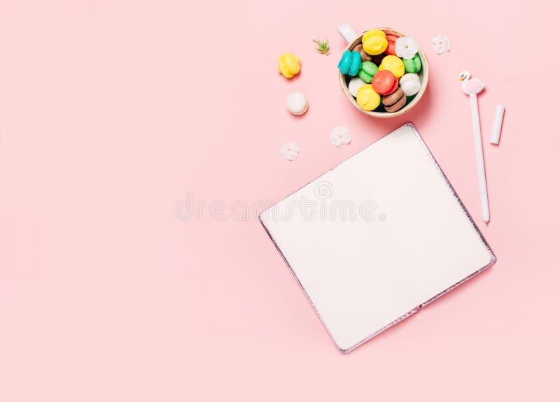 Taza de macarons y libreta en fondo rosado foto de archivo