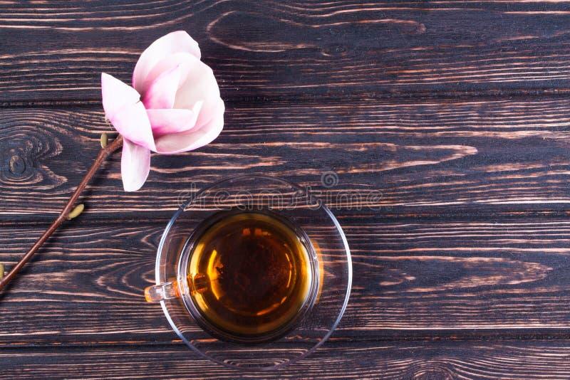 Taza de magnolia del té negro y de la flor en los tableros de madera fotos de archivo libres de regalías