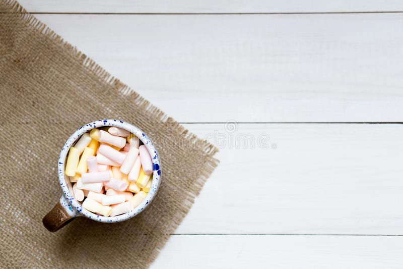 Taza de melcochas coloridas en la tabla de madera, visión superior fotografía de archivo libre de regalías