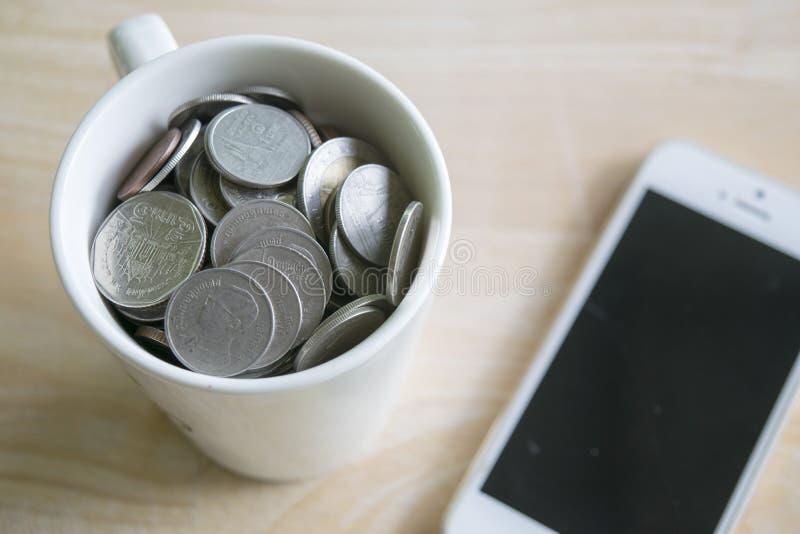 Taza de moneda y de teléfono imagenes de archivo