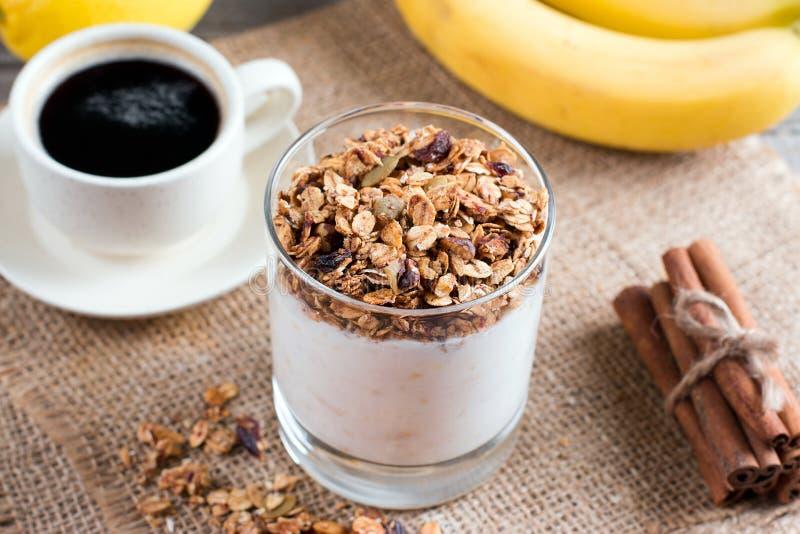 Taza de muesli sano del desayuno con el plátano y el yogur foto de archivo
