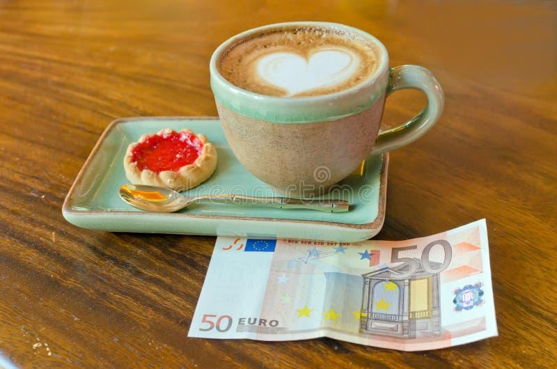 Taza de nota del café y del euro imagen de archivo