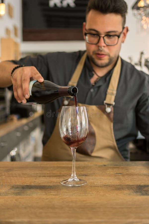 Taza de ofrecimiento del camarero de vino en un pub fotografía de archivo