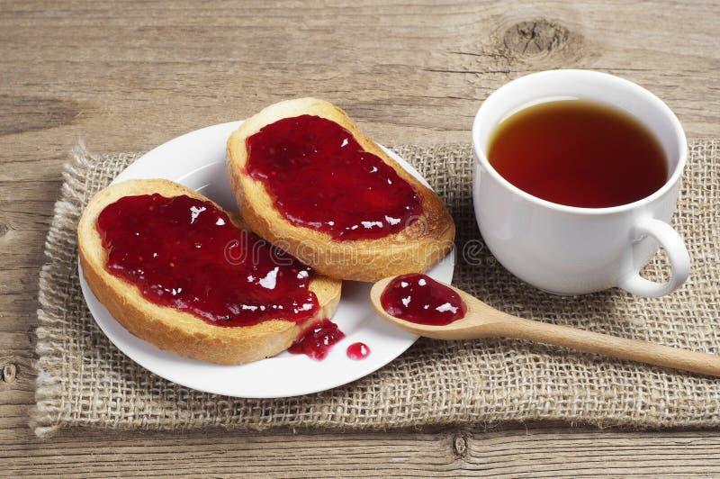 Taza de pan del té y blanco con la mermelada de fresa imagenes de archivo