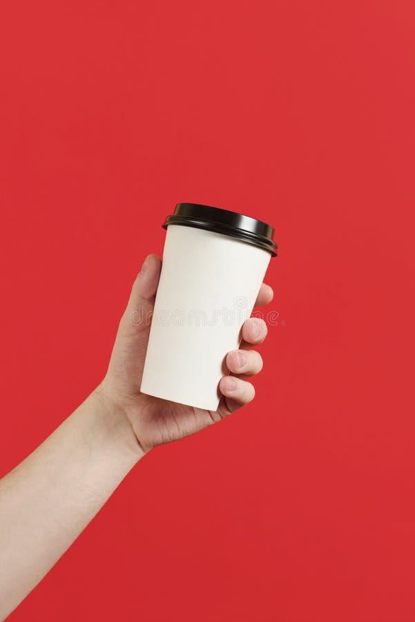 Taza de papel de caf? o de t? en un fondo rojo La maqueta de la mano masculina que sosten?a la taza de papel aisl? Maqueta de la  imagen de archivo