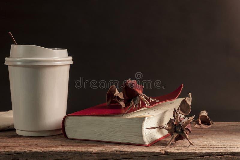 Taza de papel de café y de un libro en la tabla de madera imagen de archivo