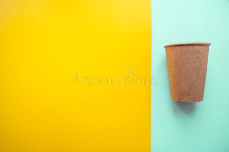 Taza de papel en fondo brillante del color fotografía de archivo