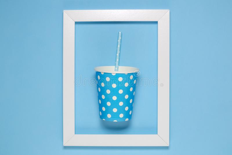 Taza de papel rosada llana con la paja de beber enmarcada en el papel pintado azul llano fotografía de archivo