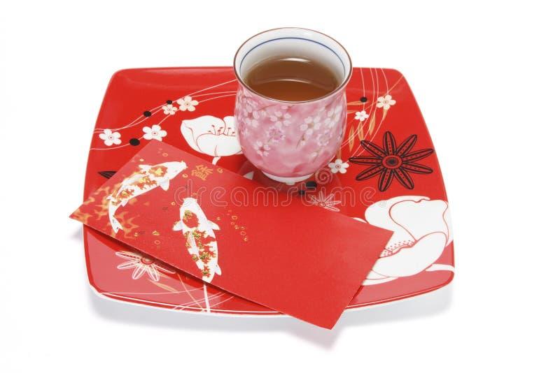 Taza de paquete chino del té y del rojo en la placa imágenes de archivo libres de regalías