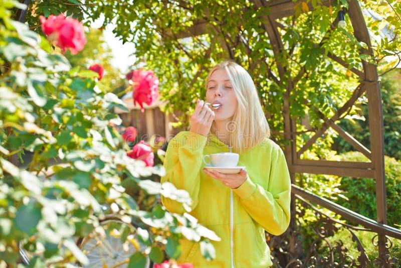 Taza de placer Goce del capuchino cremoso delicioso en jard?n floreciente Capuchino gastr?nomo de la bebida de la muchacha La muj fotos de archivo libres de regalías