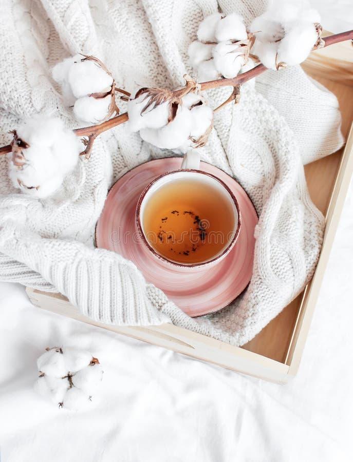 Taza de rama caliente del té del suéter hecho punto bandeja de madera de la tela escocesa del algodón en cama con los linos blanc foto de archivo