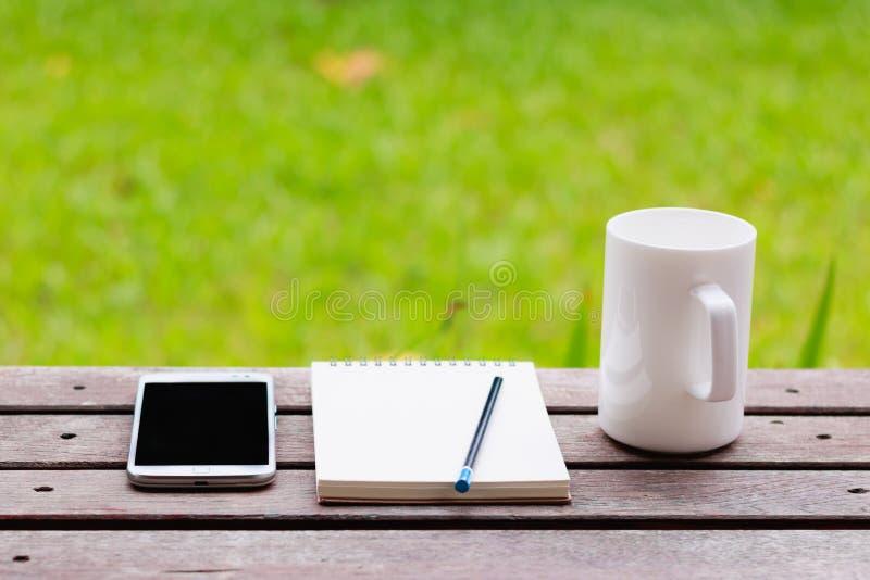 Taza de Smartphone, del cuaderno, del lápiz y de café en la tabla de madera fotografía de archivo libre de regalías