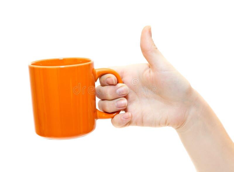 Taza de té anaranjada a disposición fotografía de archivo libre de regalías